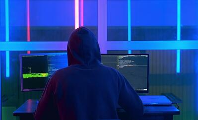 A hooded cyber attacker attempting to infiltrate cybersecurity measures on a computer | Varay Managed IT, San Antonio & El Paso