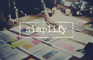 Cluttered business desk with the word simplify | Varay, El Paso