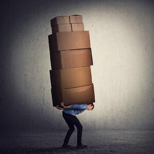 Man bent over under a load of heavy boxes to symbolize having to carry the burden of IT issues.