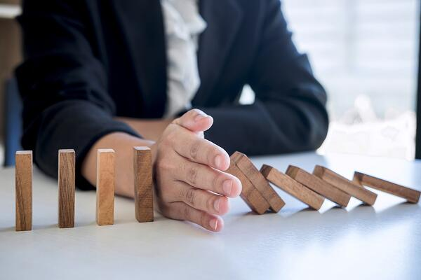 Hand blocking a row of falling dominos, signifying risk avoidance/business