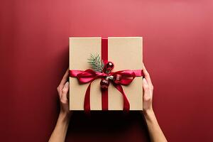 Woman's hands holding a Christmas package on a red background.