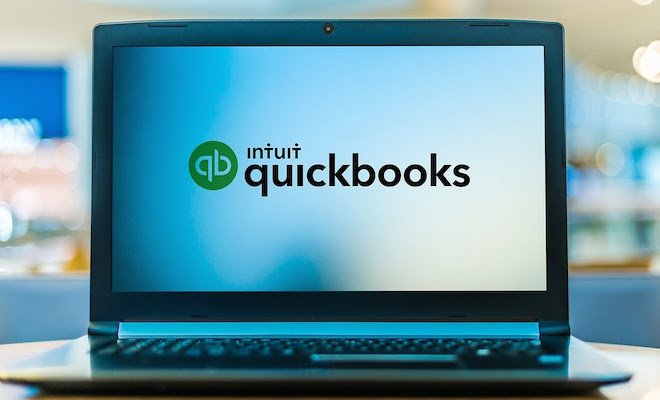 A black laptop with the QuickBooks logo on the screen.