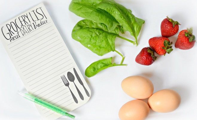Blank grocery list with strawberries and eggs on the table next to it.