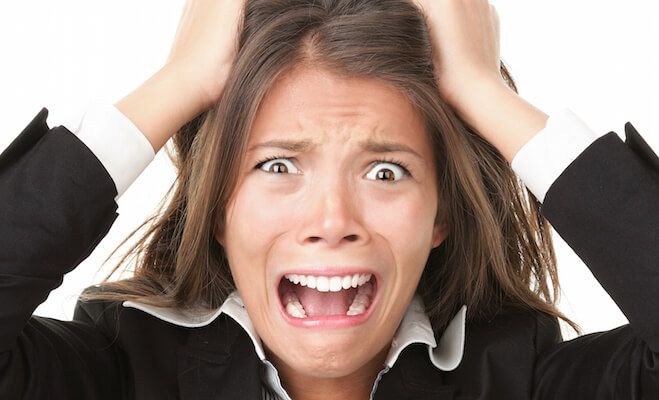 Funny close up of a business woman stressed out with her hands on her head, yelling.