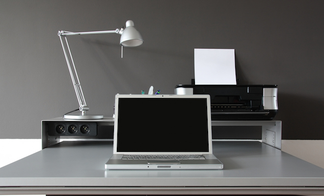 Modern minimalist black-and-white home office with a laptop, printer and adjustable lamp.