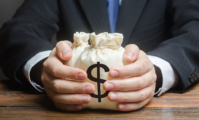 Torso shot of a businessman holding a bag with a dollar sign in between both hands.