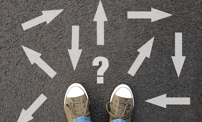 feet standing on asphalt with a multitude of arrows in different directions and a question mark.